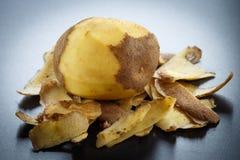 Raw peeled potatoes and potato peelings Royalty Free Stock Photo