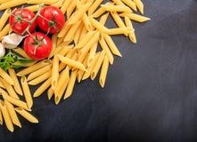 Raw penne pasta on black background. Raw penne on black background Stock Image