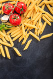 Raw penne pasta on black background. Raw penne on black background Royalty Free Stock Photography