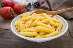 Raw penne pasta in bowl Royalty Free Stock Image