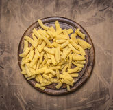 Raw penne pasta on a round cutting board on wooden rustic background top view close up Royalty Free Stock Photography