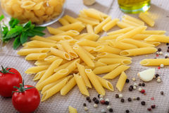 Raw penne pasta with vegetables. Raw penne pasta with tomatoes and pepper Royalty Free Stock Photo