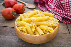 Raw penne pasta in wooden bowl Royalty Free Stock Images