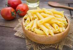 Raw penne pasta in wooden bowl Stock Photography