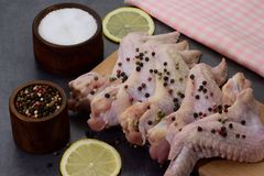 Raw peppered and salted chicken wings on cutting board. With lemon slices on dark background Royalty Free Stock Image