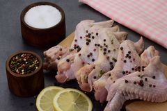 Raw peppered and salted chicken wings on cutting board. With lemon slices on dark background Stock Images