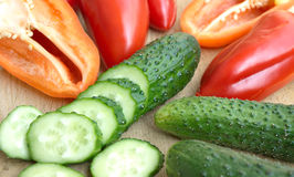 Raw peppers and cutted cucumbers on brown kitchen Stock Image
