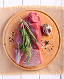 Raw piece of beef and rosemary on board Stock Photo