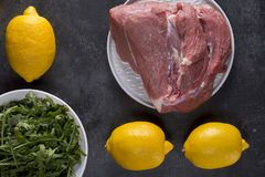 Raw piece of meat with lemon on black stone background royalty free stock photos