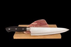 Raw piece of meat on a wooden board on a black background. Large raw piece of meat on a wooden board on a black background Royalty Free Stock Images
