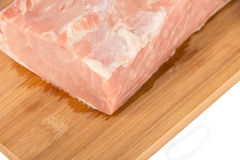Raw piece of meat on a wooden board on a white background. Large raw piece of meat on a wooden board on a white background Stock Photos