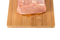 Raw piece of meat on a wooden board on a white background. Large raw piece of meat on a wooden board on a white background Royalty Free Stock Image