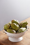 Raw pile of artichokes on colander Royalty Free Stock Photography