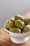 Raw pile of artichokes on colander Royalty Free Stock Photo