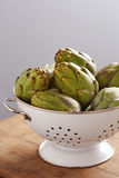 Raw pile of artichokes on colander Royalty Free Stock Image
