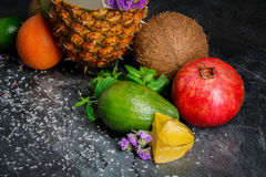 Raw pineapple, red garnet and ripe avocado. Green mint, coconut and carambola. Close-up of fruits on a black background. Stock Photography