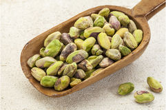 Raw pistachio nuts on a scoop. A wooden scoop od raw pistachio nuts on a rough white painted barn wood background Royalty Free Stock Image