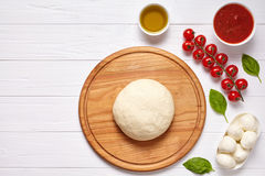 Raw pizza dough with baking ingredients on cutting board: dough, mozzarella, tomatoes sauce, basil, olive oil, cheese. Spices. Italian margherita preparation Royalty Free Stock Photos