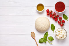 Raw pizza dough with baking ingredients: mozzarella cheese, tomatoes sauce, basil, olive oil, cheese, spices. Italian. Margherita preparation on white wooden Royalty Free Stock Photos