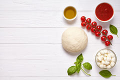 Raw pizza dough with baking pastry ingredients: mozzarella, tomatoes sauce, basil, olive oil, cheese, spices. Italian traditional pizza margherita preparation Royalty Free Stock Photo