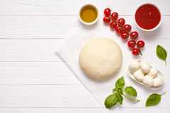 Raw pizza dough with baking recipe ingredients: mozzarella, tomatoes sauce, basil, olive oil, cheese, spices. Italian. Margherita preparation on white wooden Royalty Free Stock Photos