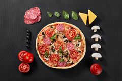 Raw pizza dough with ingredients for cooking vegetarian pizza on the dark stone surface with border, top view. Healthy food Royalty Free Stock Images