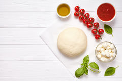 Raw pizza dough with ingredients: mozzarella, tomatoes sauce, basil, olive oil, cheese, spices. Italian margherita on. Raw pizza dough with ingredients Stock Photos