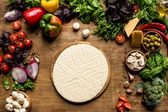 Raw pizza dough and ingredients. Top view of raw pizza dough and fresh ingredients on wooden tabletop Royalty Free Stock Photography