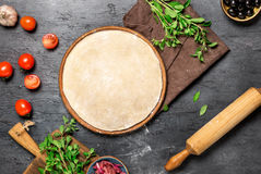 Raw pizza dough with set ingredients for cooking vegetarian pizz Stock Image