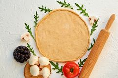 Raw pizza dough on the white background with free copy space. Dough with rolling pin and ingredients for vegetarian pizza. Mushrooms, black olives, tomato and Stock Photography