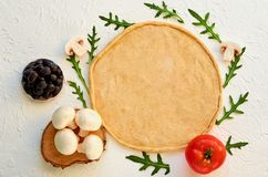 Raw pizza dough on the white background with free copy space. Dough with ingredients for veggie pizza: mushrooms, olives, rucola. Raw pizza dough on the white Stock Photography