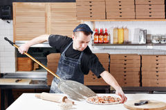 Raw pizza ready to bake. Cook in a blue apron in the kitchen. with a shovel in his hands. boxes for food delivery on Stock Image