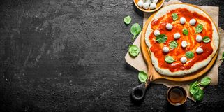 Raw pizza. Rolled out dough on a cutting Board with tomato paste, mozzarella and spinach. On rustic background royalty free stock photo