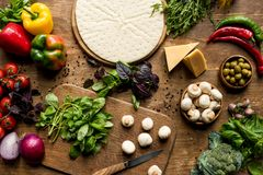 Raw pizza. Top view of raw pizza dough and fresh ingredients on wooden tabletop royalty free stock photography