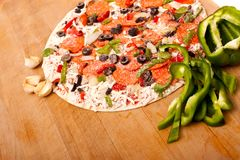 Raw pizza with vegetables and pepperoni Stock Photo