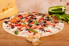 Raw pizza with vegetables and pepperoni Stock Images