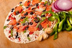Raw pizza with vegetables and pepperoni Stock Image