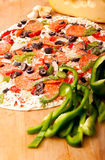 Raw pizza with vegetables and pepperoni. Raw pizza with pepperoni, bell peppers, black olives and onions Stock Photos