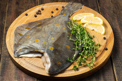 Raw plaice with pepper, thyme and lemon on the board. Raw plaice with pepper, thyme and lemon on a round cutting board and wooden table Royalty Free Stock Image