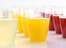 Raw of plastic glasses with fresh juice Royalty Free Stock Images