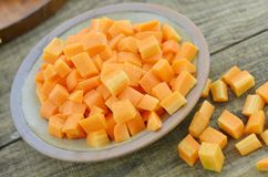 Raw plate with fresh diced carrot on wooden table. Closeup Stock Photography