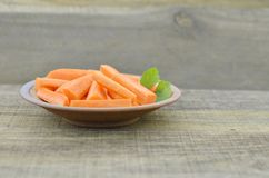 Raw plate with fresh sticks carrot on wooden rustic. Raw plate with fresh sticks carrot on wooden background Stock Photo