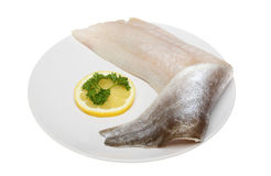 Pollock fillet. Raw pollock fish fillet on a plate with lemon and parsley isolated against white royalty free stock image