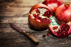Raw pomegranate with knife on the table. Raw pomegranate cut in half with knife on the table Stock Photos