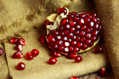 Raw pomegranate with seeds on sacking Royalty Free Stock Photo