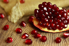 Raw pomegranate with seeds on wood Royalty Free Stock Photography