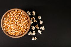 Raw popcorn in wooden bowl on black background and space for text, top view Stock Photography