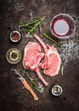 Raw Porco Iberico meat ribs cutlet with ingredients and glass of red wine on rustic metal background Stock Images