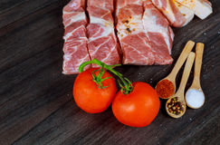 Raw pork bacon slices, rashers, spices, peppercorns, garlic, bay laurel leaves and red fresh cherry tomatoes. On black slate board, close up, high angle view Royalty Free Stock Images