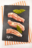 Raw pork belly with crushed peppercorn, coarse salt, garlic and. Fresh bay leaf on slate Stock Photography